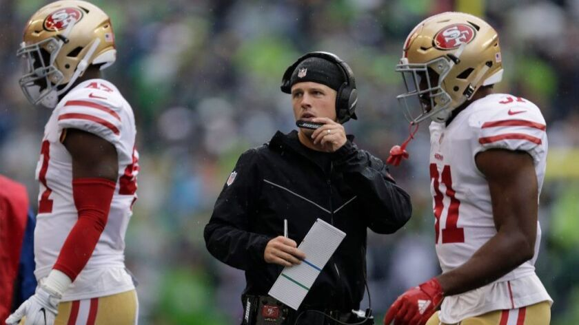 San Francisco receivers coach and passing-game specialist Mike LaFleur talks into his headset during