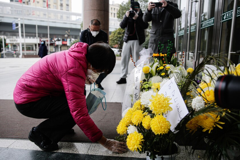 A mourner lays flowers in honor of Dr. Li Wenliang in Wuhan, China.