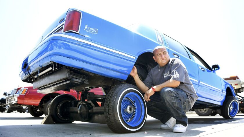 Eli Garcia with his car during the Torres Empire Los Angeles Super Show, a lowrider event and auto e