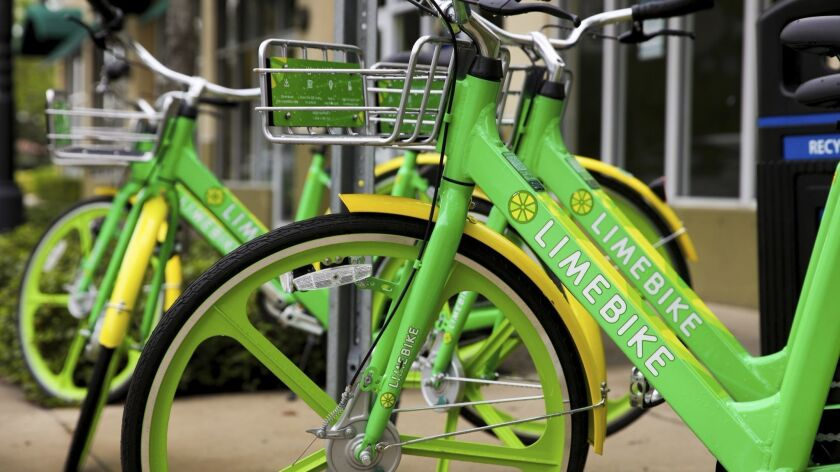 In this Oct. 25, 2017 photo, LimeBikes commuter bikes sit parked near the Miami Shores Business Dist