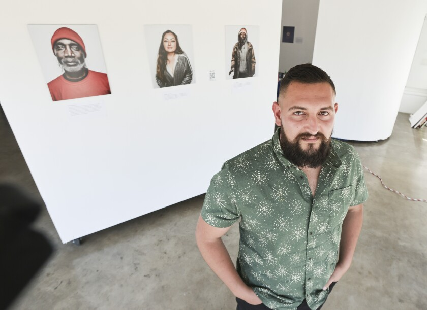 Photographer and homeless advocate Jordan Verdin poses for photos with his work.