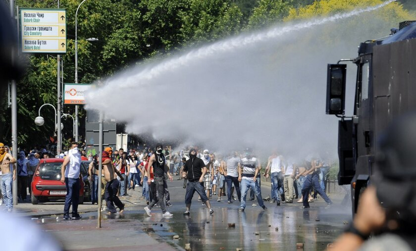 Ethnic Albanians clash with the police in Macedonia's capital Skopje on Friday, July 4, 2014. Hundreds of stone-throwing ethnic Albanians protesting a Macedonian court ruling have clashed with police, who fired water cannon and tear gas at the crowd to prevent them from storming a court building. Police said about 2,000 people gathered in Macedonia's capital Skopje on Friday to protest the life sentences imposed this week on six ethnic Albanian Muslims convicted of murdering five Christian fishermen, in an alleged plot to destabilize the country (AP Photo/Boris Grdanoski)
