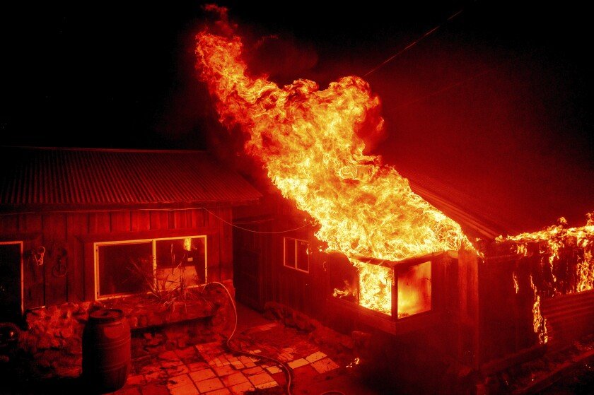 Flames shoot from the window of a one-story home in the middle of the night, casting a red glow