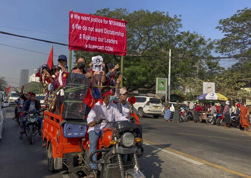 Manifestantes hacen un saludo con tres dedos en alto, símbolo de la resistencia contra el golpe militar