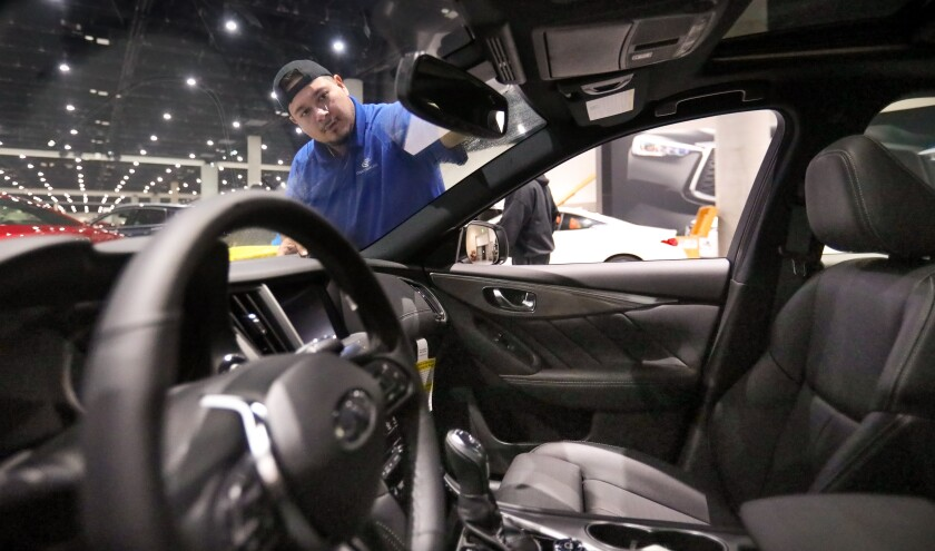 Francisco Barraza cleans the front window of a 2020 Infiniti at the San Diego Convention Center in advance of the San Diego International Auto Show that opens on New Year's Day, Jan. 1, and runs through Sunday, Jan. 5.