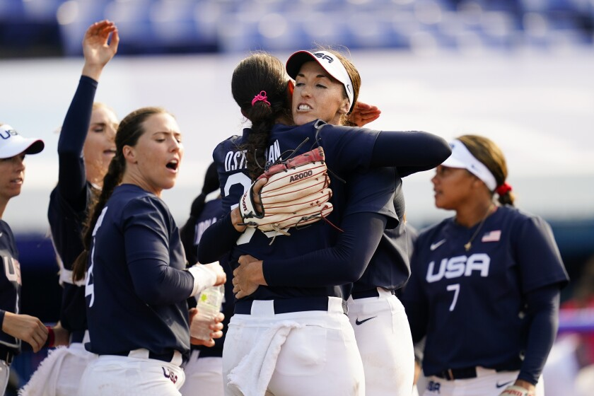 Monica Abbott and Cat Osterman hug as other players celebrate.
