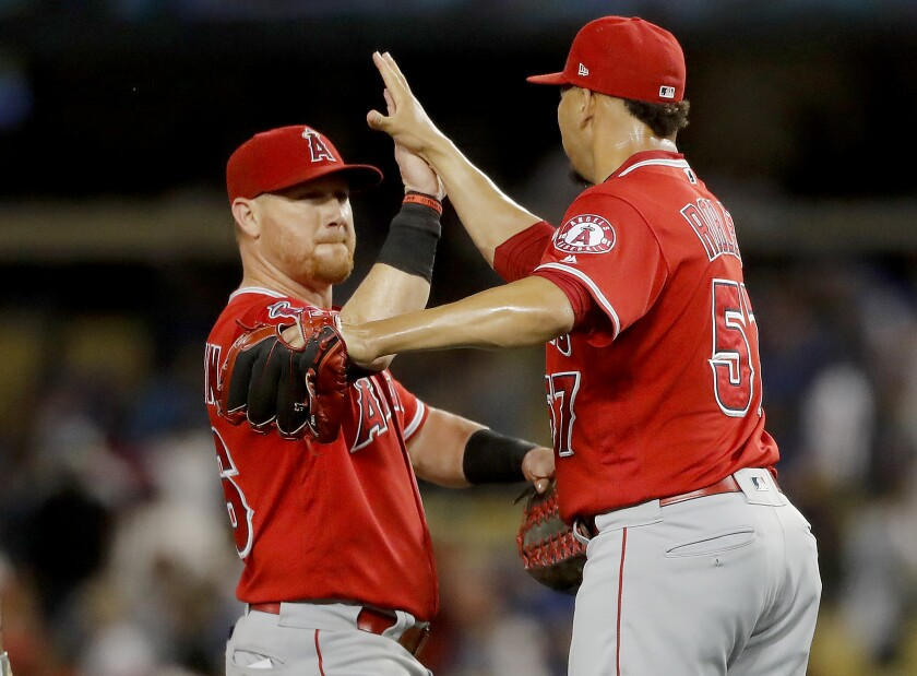 Angels right fielder Kole Calhoun and pitcher Hansel Robles celebrate a 3-2 victory over the Dodgers on Wednesday at Dodger Stadium.