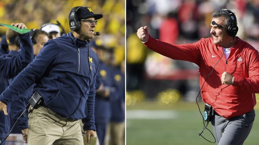 FILE - At left, in an Oct. 13, 2018, file photo, Michigan head coach Jim Harbaugh signals to his off