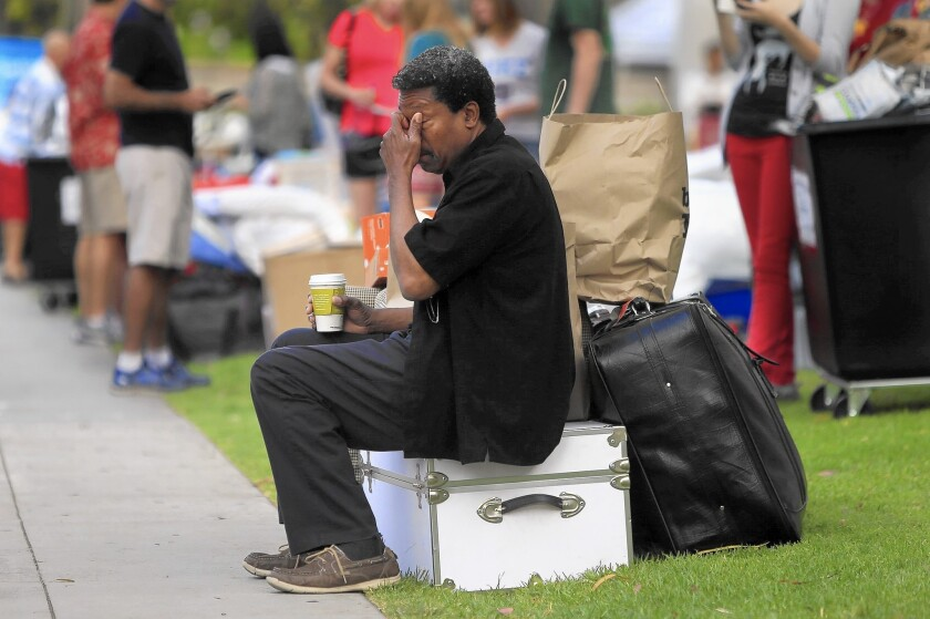 A parent rubs his eyes as he sits on his daughter's footlocker during Move-In Day at USC.