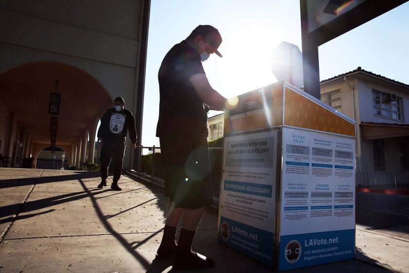 A man drops his ballot into an official ballot drop box