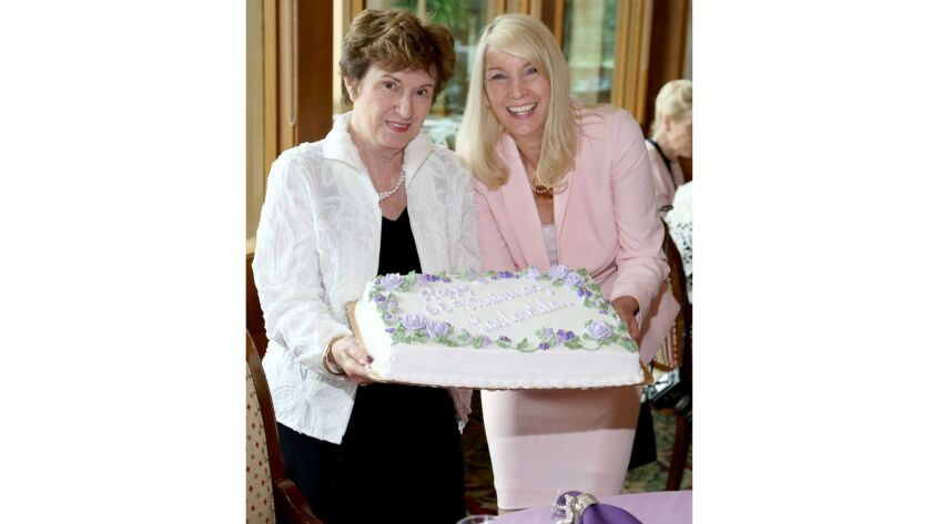 Installing officer Anna Brewer, left, and President Nancy Stone display the cake in celebration of t