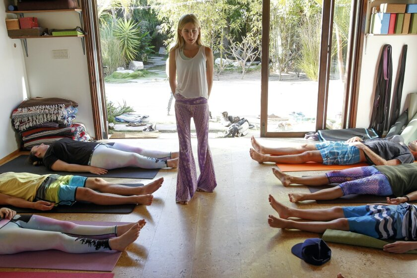 Yoga teacher Jaysea DeVoe, 12, softly speaks to members of her yoga class at Bergamot Spa & Boutique in Encinitas on Tuesday.