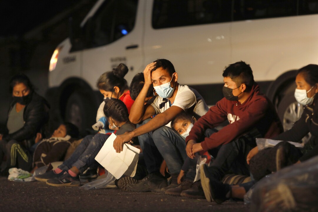 A group of migrant adults and children sit on the ground next to a van at night