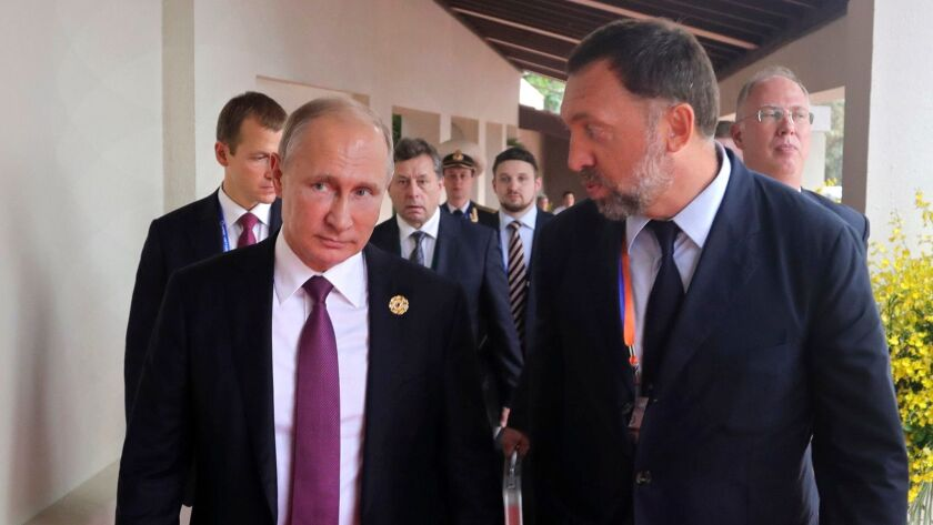 Russian President Vladimir Putin and Russian metals magnate Oleg Deripaska attend the APEC Business Advisory Council dialogue in Danang, Vietnam, on Nov. 10, 2017.