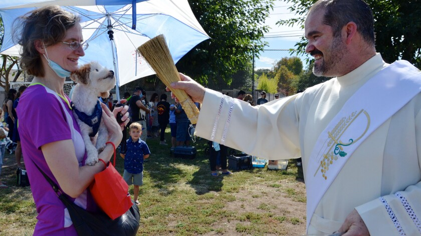 Deacon Francisco Javier Martin of St. Joachim Catholic Church in Costa Mesa sprinkles holy water on a dog.
