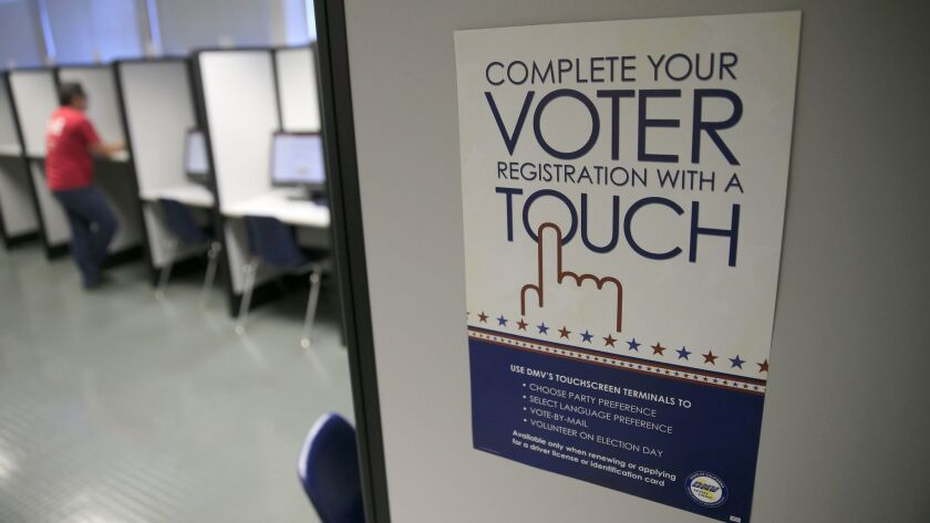 A sign advertises a touchscreen machine, a new process for voter registration at the Department of Motor Vehicles in Santa Ana.