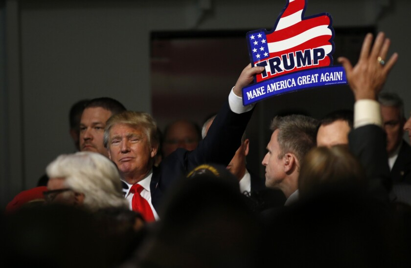 Republican presidential candidate Donald Trump holds one of his signs after a rally in Mount Pleasant, S.C.