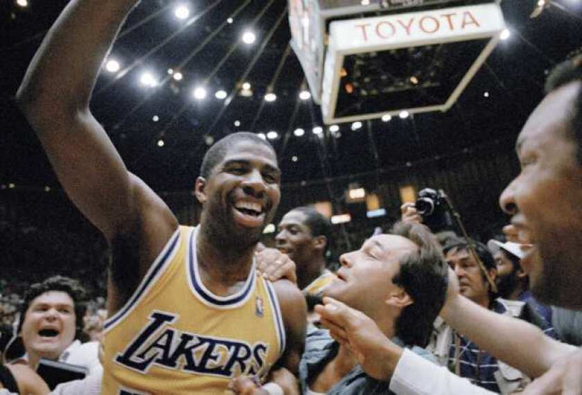 Magic Johnson celebrates with fans after the Lakers win the championship in 1987.