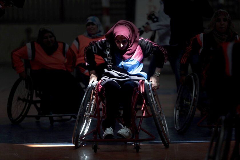 In this Saturday, May 28, 2016 photo, a disabled Palestinian woman takes part in a basketball training session for the territory's first female wheelchair basketball team in the Khan Younis refugee camp, southern Gaza Strip. In 2015, the International Committee of the Red Cross brought top U.S. coa