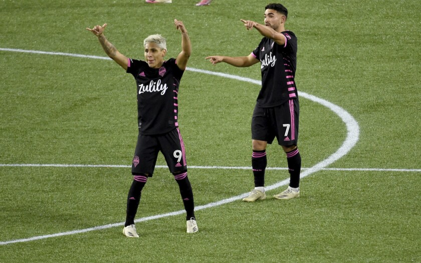 Seattle Sounders forward Raul Ruidiaz, left, and midfielder Cristian Roldan celebrate after the Sounders scored during the second half of an MLS soccer match against the Vancouver Whitecaps in Portland, Ore., Tuesday, Oct. 27, 2020. (AP Photo/Steve Dykes)
