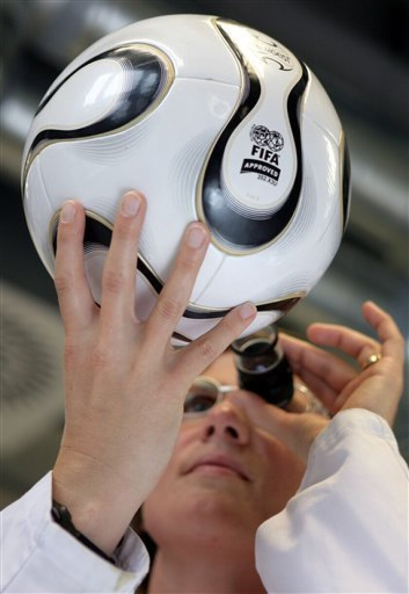 """FILE - This May 31, 2006 file picture shows lab assistant Stefanie Jonke checking the outer surface of a """"Teamgeist"""" World Cup soccer ball at a laboratory of the Bayer company in Leverkusen, Germany. Adidas countered criticism Monday May 31, 2010 that its World Cup ball is difficult to control and"""