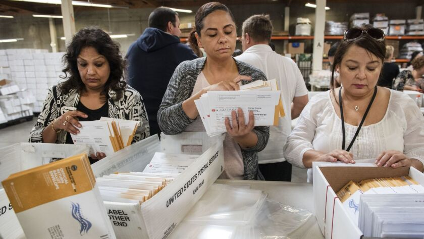 Employees of the Orange County Registrar of Voters sort through mail-in ballots in Santa Ana.