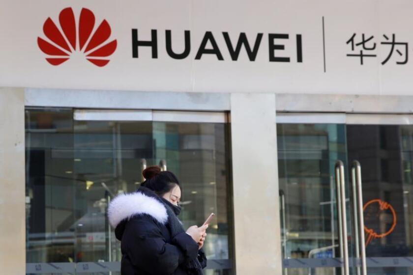 Una joven utiliza su teléfono móvil ante una tienda de la firma china Huawei en Pekín, China, EFE/Archivo