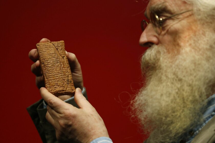 Irving Finkel, curator in charge of cuneiform clay tablets at the British Museum, poses with the 4000 year old clay tablet containing the story of the Ark and the flood during the launch of his book 'The Ark Before Noah' at the British Museum in London, Friday Jan. 24, 2014. The book tells how he d