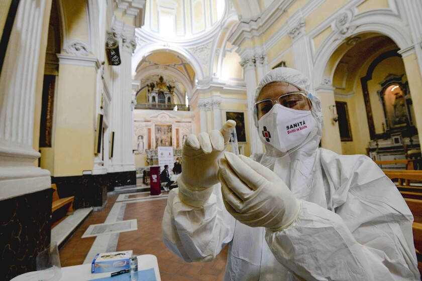A medical worker prepares to conduct a coronavirus test in Naples, Italy.