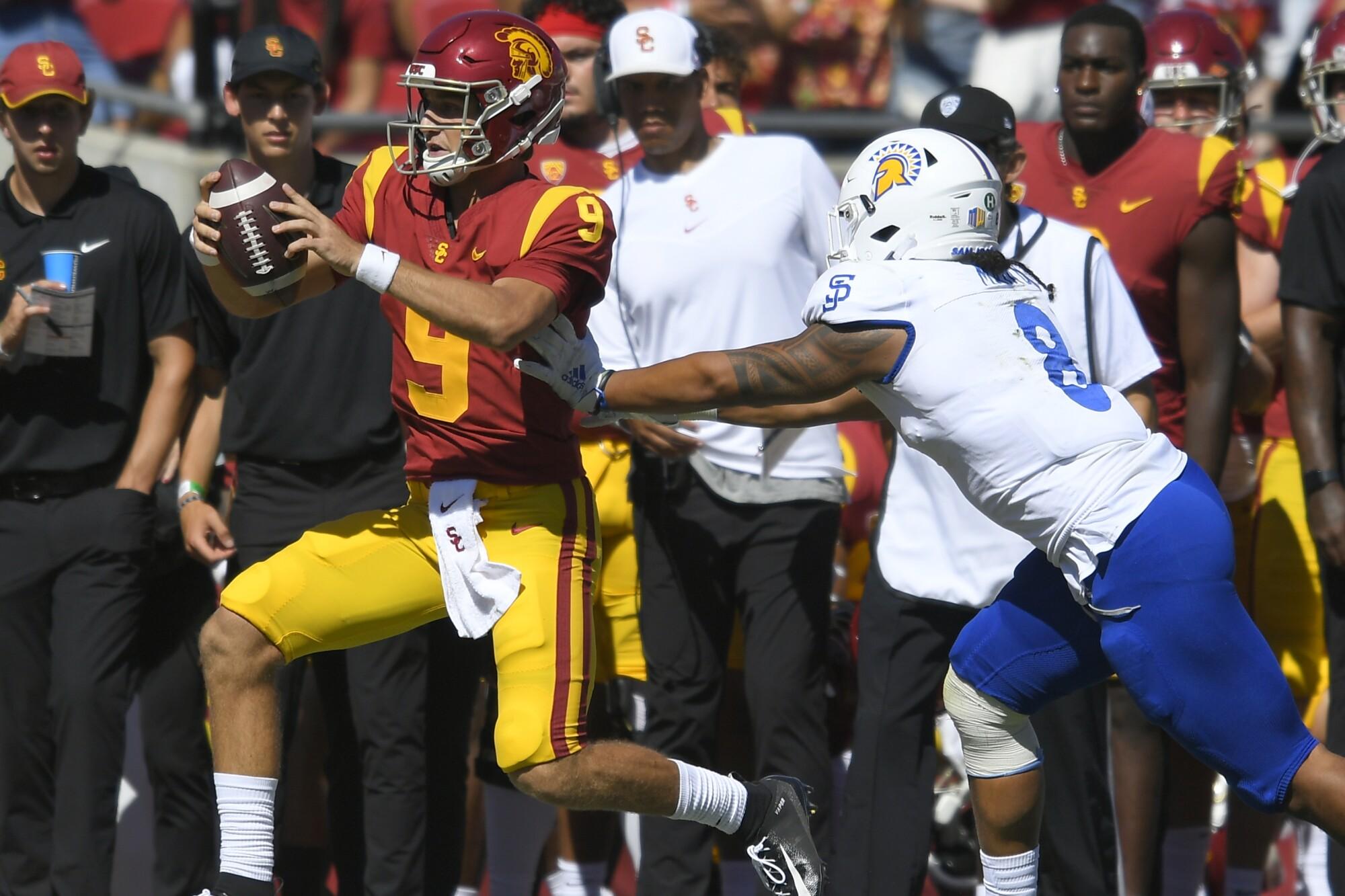San Jose State linebacker Alii Matau pushes USC quarterback Kedon Slovis out of bounds