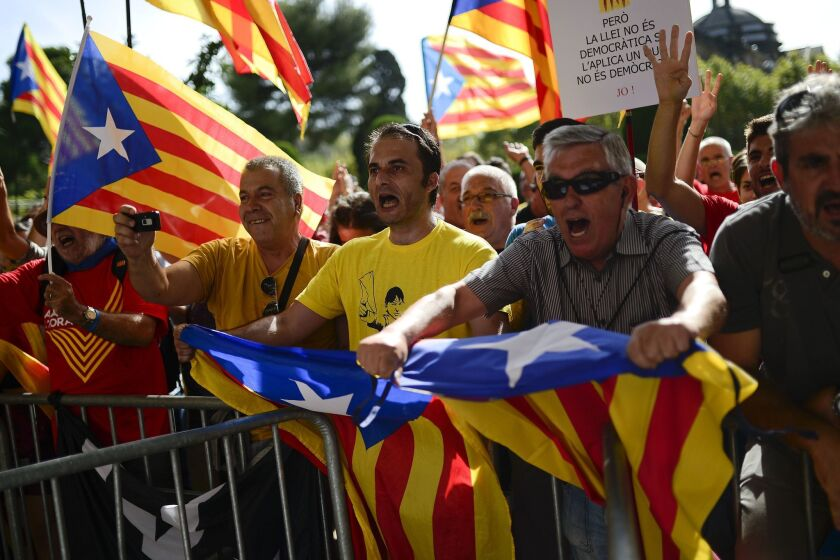 Catalans wave Esteladas, their independence flags, before the regional parliament's passage of a measure approving a referendum on breaking away from Spain.