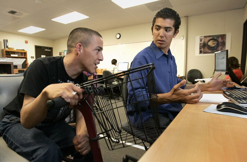 Horus Ocampo (left) worked with Eric Noriega on an English project at Palomar College. Ocampo's motorized wheelchair was stolen this month and he has been using a loaner. The wheelchair was found, but it was damaged and is now being repaired. (John Gastaldo / Union-Tribune)