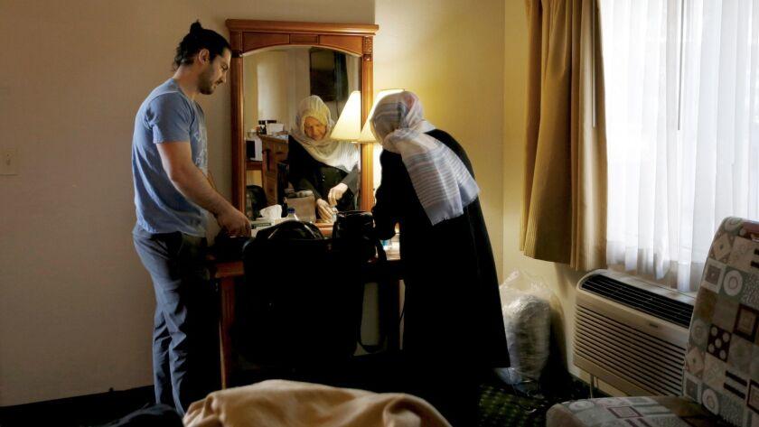 Siavosh Naji-Talakar, left, helps his grandmother Marzieh Moosavizadeh, 75, pack at their hotel near LAX in El Segundo.