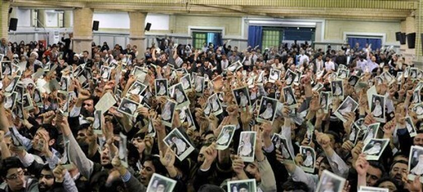 In this photo released by the official website of the Iranian supreme leader's office, Iranian well wishers attending the speech of Supreme Leader Ayatollah Ali Khamenei hold up his picture at a mosque inside the leader's housing compound in Tehran, Iran, Saturday, Feb. 16, 2013.  Khamenei said Sat
