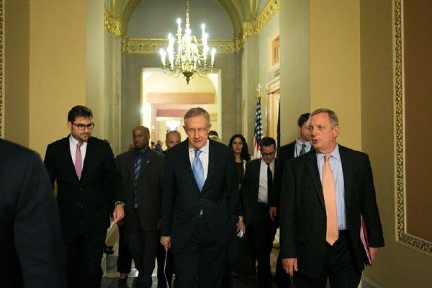 Senate Majority Leader Harry Reid (D-Nev.) walks with Sen. Dick Durbin (D-Ill.) after a joint caucus meeting on Capitol Hill.