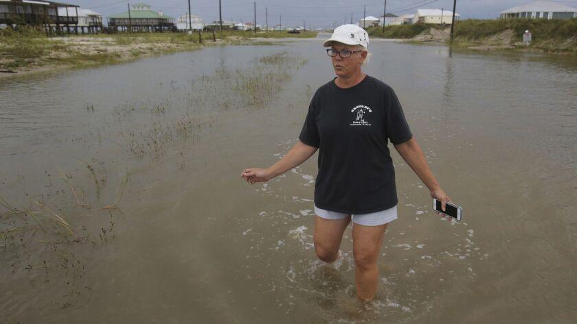 Susan Jones walks through a flooded road from Tropical Storm Gordon, Wednesday, Sept. 5, 2018, in Da