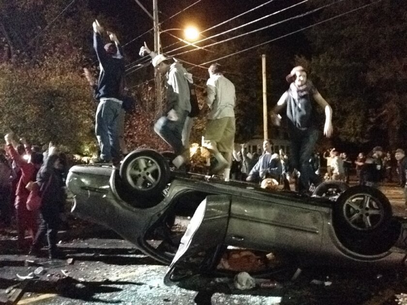 People stand atop an overturned car in Keene, N.H.