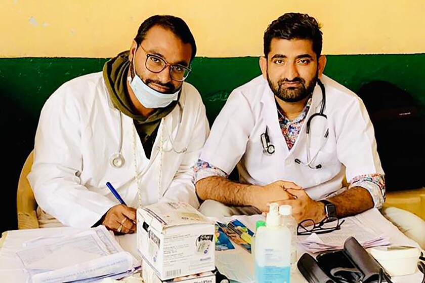 In this October 2019 photo provided by Bharat Sangwan, Joginder Chaudhary, left, and his friend and colleague Sangwan volunteer at a medical camp for women. After the virus killed the 27-year-old Chaudhary in late July 2020, his mother wept inconsolably. With her son gone, Premlata Chaudhary said, how could she go on living? Three weeks later, on Aug. 18, the virus took her life, too — yet another number in an unrelenting march toward a woeful milestone. (Courtesy of Bharat Sangwan via AP)