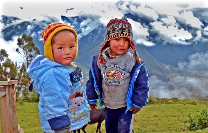 PERU, CUZCO: Children wait at a popular viewpoint outside Cuzco while their mothers sell souvenirs to passing motorists.