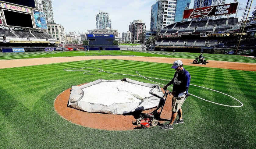 Padres head groundskeeper Luke Yoder edges the pitcher's mound the day before opening day in San Diego 2012.