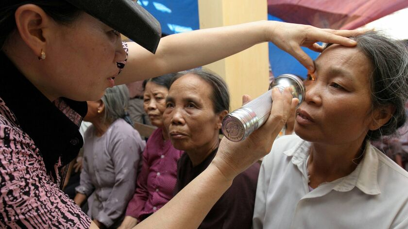 A woman receives an eye examination for