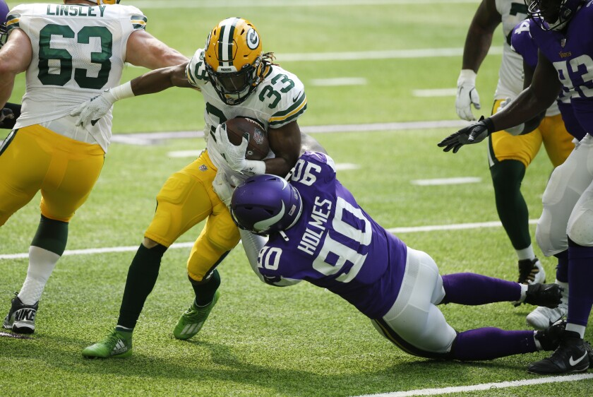 Green Bay Packers running back Aaron Jones (33) tries to break a tackle by Minnesota Vikings defensive tackle Jalyn Holmes during the first half of an NFL football game, Sunday, Sept. 13, 2020, in Minneapolis. (AP Photo/Bruce Kluckhohn)