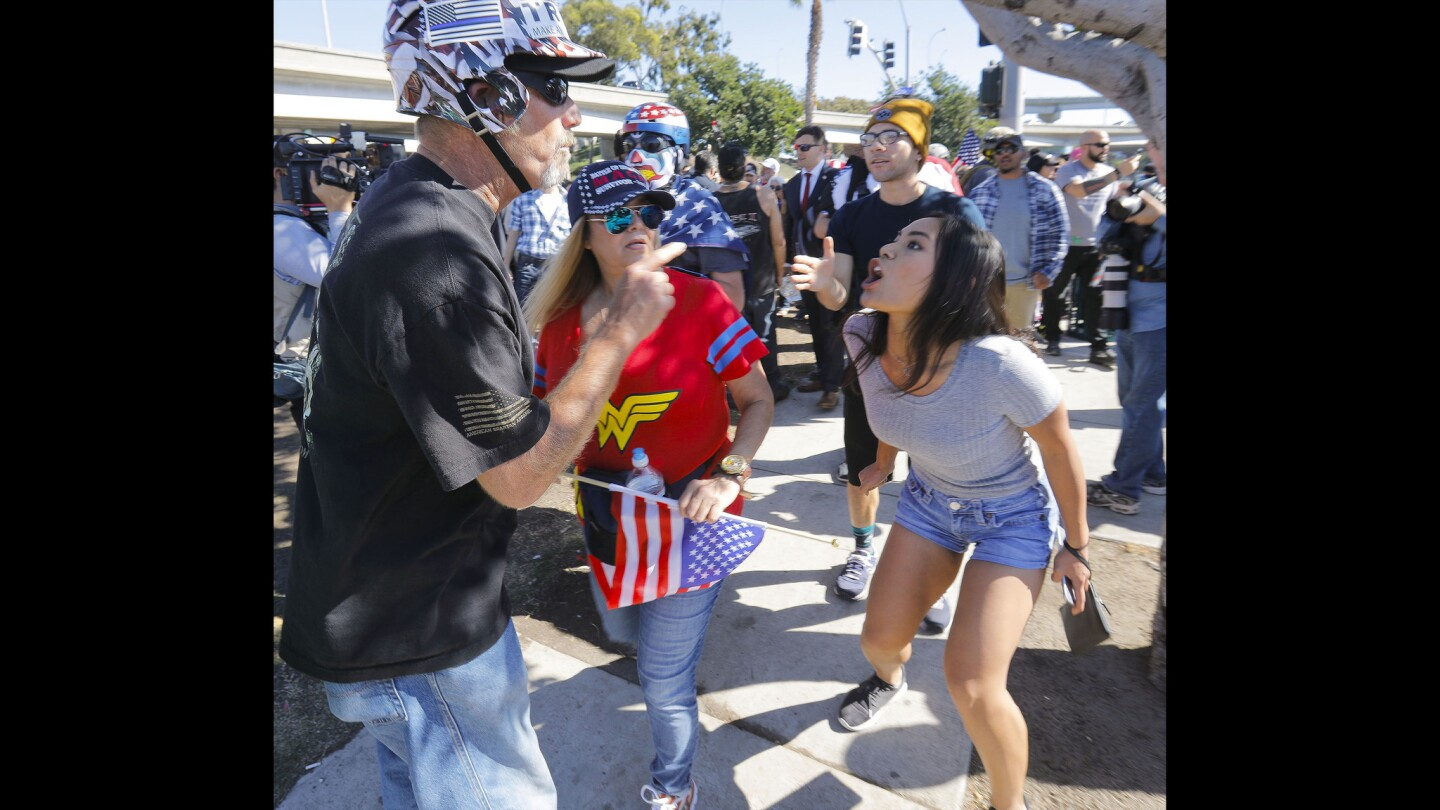 A person who attended the Bordertown Patriots' Patriot Picnic at Chicano Park, left, and a Chicano Park supporter, right, came face-to-face as the Bordertown Patriots group was being escorted out of the park by police.