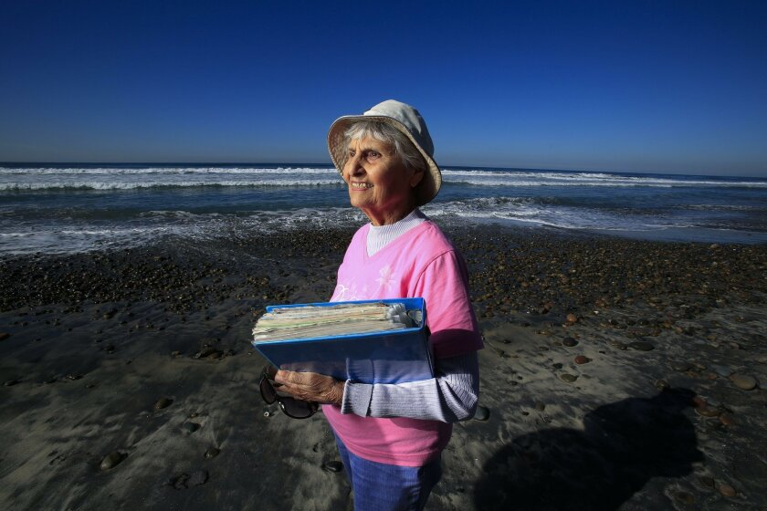 Tensia Moriel Trejo of Del Mar holds a scrapbook of Penguin Plunge events. She's missed just one of the New Year's Day swim events at Del Mar Beach in the past 30 years.
