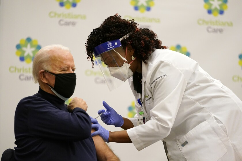 A nurse practitioner gives Joe Biden, holding his rolled-up sleeve, a shot in his upper arm.
