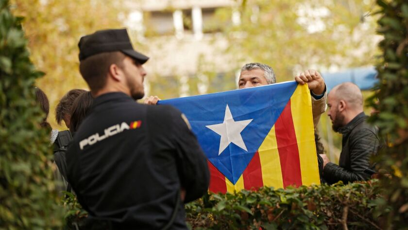 "A man holds up an ""esteladas"", or Catalonia independence flag, in front of a Spanish national police"