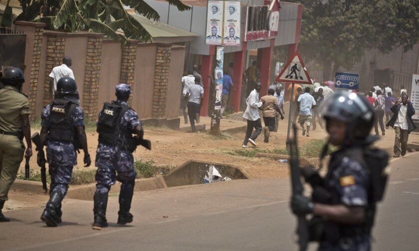 Police firing tear gas and stun grenades chase supporters of opposition leader Kizza Besigye, on the street outside his party headquarters, in Kampala, Uganda Friday, Feb. 19, 2016. Police in Uganda arrested opposition leader Kizza Besigye at his party's headquarters Friday after heavily armed police surrounded the building and fired tear gas and stun grenades at his supporters who took to the streets. (AP Photo/Ben Curtis)