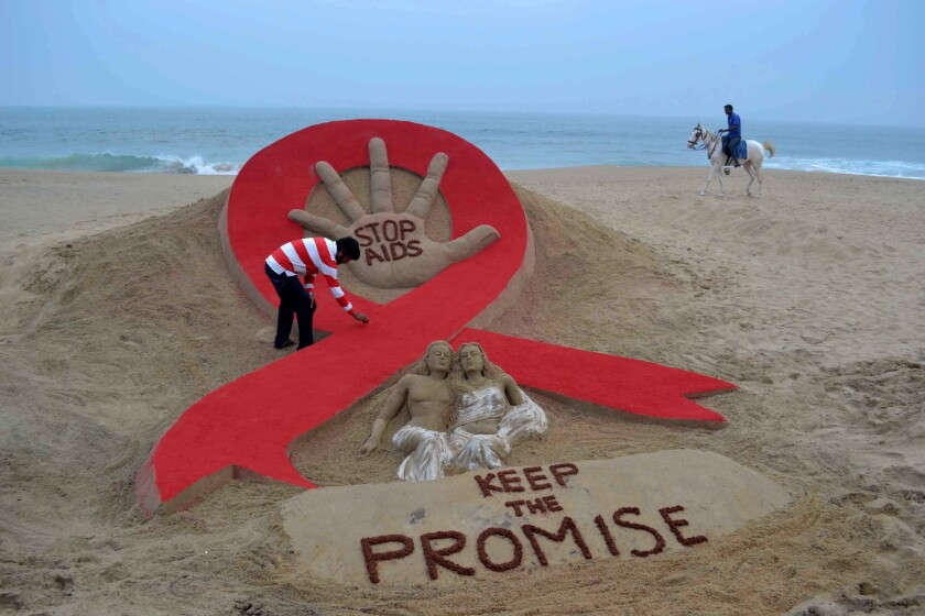 Indian sandartist Sudersan Pattnaik gives the final touches to a sand sculpture on the eve of World AIDS Day, an annual event to raise awareness about HIV/AIDS.