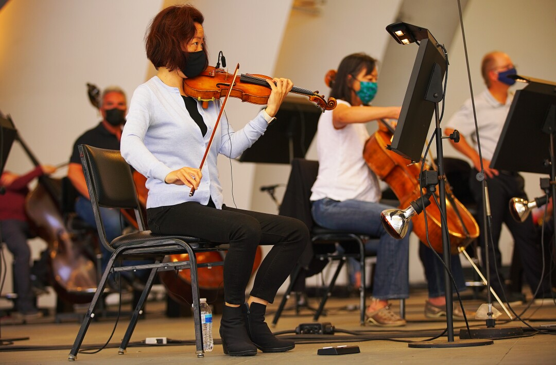 Musicians play stringed instruments at the L.A. Phil