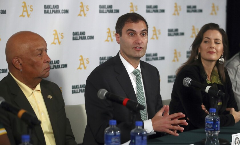 Oakland Athletics President Dave Kaval, center, speaks at a news conference
